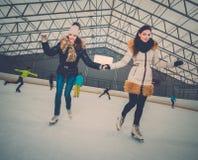 Flickor på att åka skridsko isbanan royaltyfria bilder