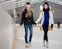 Flickor på att åka skridsko isbanan royaltyfria foton