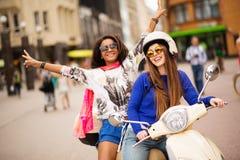Flickor på en sparkcykel i en stad Royaltyfri Bild