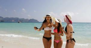 Flickor på stranden som tar det Selfie fotoet på den cellSmart telefonen, gladlynta kvinnor i bikini och Straw Hats On Summer Hol