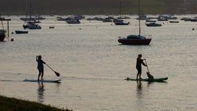 Flickor paddlar logi på den Exe breda flodmynningen i Devon UK Royaltyfri Bild
