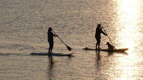 Flickor paddlar logi på den Exe breda flodmynningen i Devon UK Royaltyfri Fotografi