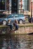 Flickor sitter på kanalbanken i Amsterdam Royaltyfri Foto