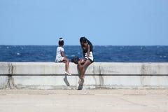 Flickor sitter på stranden och ser havet i Havana Cuba royaltyfria foton
