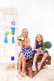 Flickor sitter på träaskar Royaltyfri Bild