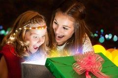 Flickor som öppnar gåva med stor förväntan Arkivfoton