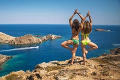 Flickor som öva yoga ovanför havet arkivfoto