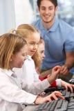 Flickor som använder datorer i grupp med lärare fotografering för bildbyråer