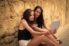 Flickor som använder minnestavlan royaltyfria foton