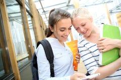 Flickor som använder mobiltelefonen på skolan Arkivbilder