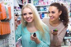 Flickor som applicerar den near spegeln för mascara Royaltyfria Foton