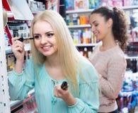 Flickor som applicerar den near spegeln för mascara Arkivbild