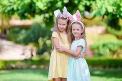 Flickor som bär kaninen, gå i ax på påskdag utomhus Ungar tycker om easter ferie Arkivbild