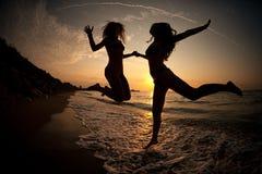 Flickor som DANSAR I SOLNEDGÅNG PÅ HAVET Fotografering för Bildbyråer