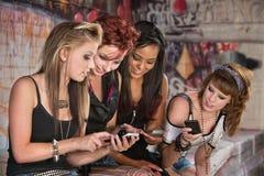 Flickor som delar information om mobiltelefon royaltyfria bilder