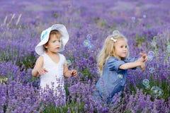 Flickor som fångar såpbubblor royaltyfria foton