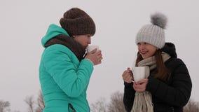 Flickor som frysas i förkylning som talar och dricker varma drinkar från exponeringsglas, skrattar att le royaltyfria bilder