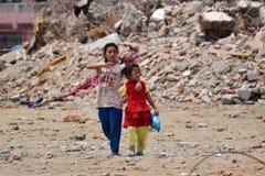 Flickor som går passerandet, kollapsade byggnad efter jordskalvkatastrof Arkivbilder