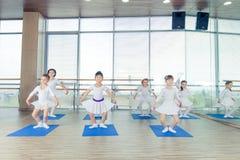 Flickor som gör gymnastiska övningar eller övar i konditiongrupp Arkivfoto