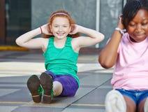 Flickor som gör sitta-UPS i fysisk utbildning Arkivbilder