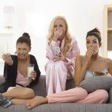 Flickor som håller ögonen på fasafilm på tv Arkivbild