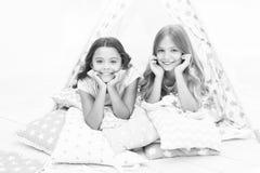 Flickor som har det roliga tipihuset Flickaktig fritid Systrar delar skvallrar ha gyckel hemma Pyjamasparti för ungar cozy arkivbild