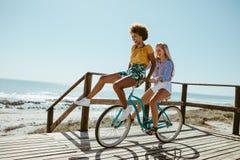 Flickor som har en stor gyckel på cykeln royaltyfri bild