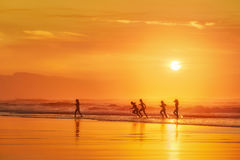Flickor som har gyckel i stranden på solnedgången Royaltyfri Foto