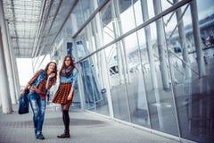 Flickor som har gyckel och skojar, medan vänta på ditt flyg med a Arkivbilder