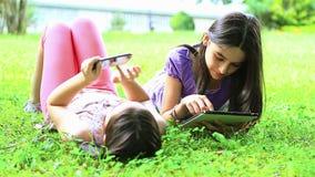 Flickor som har gyckel på den digitala minnestavlan och smartphonen lager videofilmer