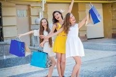 Flickor som har gyckel tillsammans Flickor som rymmer shoppingpåsar och, går Arkivbild