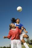 Flickor som Heading fotbollbollen under match Arkivfoton