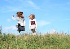 Flickor som hoppar i gräs Royaltyfri Foto