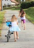 Flickor som kör och rider en cykel Royaltyfri Fotografi