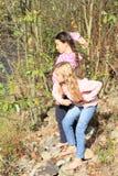 Flickor som kastar stenar till vatten Arkivbild