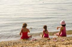Flickor som kastar stenen i havet royaltyfria foton