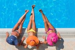 Flickor som kopplar av i en simbassäng Royaltyfri Bild