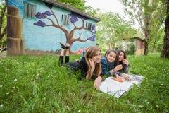 Flickor som läser en bok i parkera Fotografering för Bildbyråer