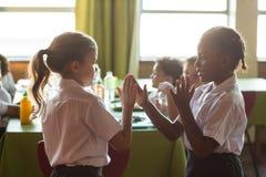 Flickor som leker applådera leken Arkivfoto
