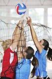 Flickor som leker för volleyboll leken inomhus Arkivfoton
