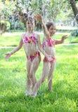 flickor som leker sprinkleren royaltyfria bilder