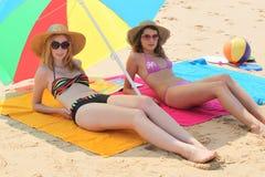 Flickor som ligger på stranden Royaltyfria Bilder