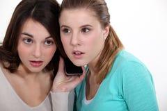 Flickor som lyssnar till en mobiltelefon Arkivfoton