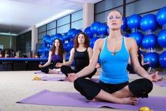 Flickor som mediterar i konditionklubba Royaltyfri Bild