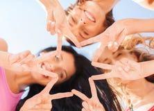 Flickor som ner ser och visar gest för finger fem Royaltyfri Bild