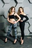 Flickor som poserar ståenden på en texturerad väggbakgrund royaltyfri fotografi