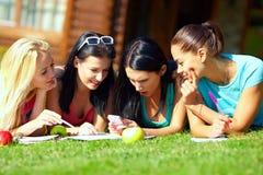 Flickor som pratar i socialt nätverk på grön lawn arkivfoto