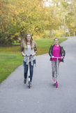 Flickor som rider deras sparkcyklar i en stad, parkerar tillsammans Royaltyfria Bilder