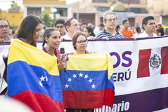 Flickor som rymmer den venezuelanska flaggan med den peruanska flaggan arkivbilder