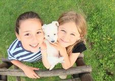 Flickor som rymmer en valp Arkivbild